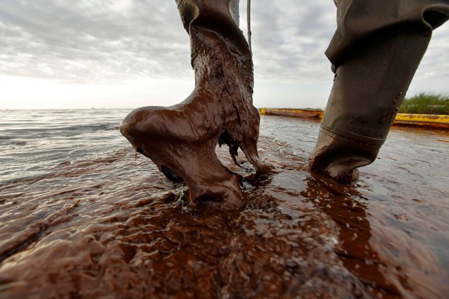 In this June 5, 2010, file photo Plaquemines Parish coastal zone director P.J. Hahn lifts his boot out of thick beached oil at Queen Bess Island in Barataria Bay, just off the Gulf of Mexico in Plaquemines Parish, La. Cleaning the oil far beyond the time the leak is capped will become the job of the U.S. Coast Guard and BP. The Houma Incident Command and Control Center in Houma, La. coordinates the different teams cleaning water from the land and sea. (AP Photo/Gerald Herbert, File)