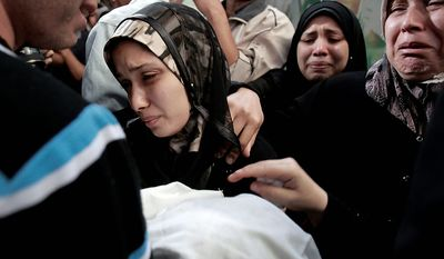 The parents of 11-month-old Palestinian baby Ahmed Masharawi, killed in an Israeli strike, hold his body during his funeral in Gaza City on Nov. 15, 2012. (Associated Press)