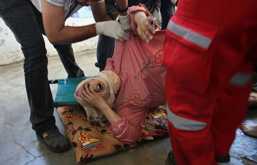 Palestinian medics help a wounded woman at her family house Nov. 15, 2012, following an Israeli air strike in Khan Younis in the southern Gaza Strip. (Associated Press)