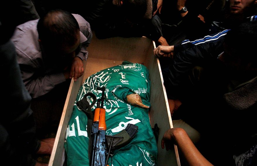 Palestinian mourners gather around the body of Hamas member Mohammad Al Hams during his funeral in Gaza City on Nov. 15, 2012. Israel barraged the Gaza Strip with airstrikes and shelling the previous day and killed the Hamas military chief in a targeted strike, launching a campaign aimed at stopping rocket attacks from Islamic militants. (Associated Press)