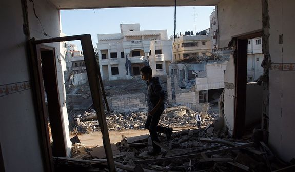 A Palestinian youth walks Nov. 15, 2012, through a damaged apartment in Gaza City hit in an Israeli strike. (Associated Press)