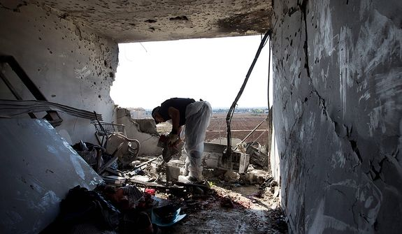 A Zaka volunteer cleans bloodstains from an apartment in a building in Kiryat Malachi, Israel, that was hit on Nov. 15, 2012, by a rocket fired from the Gaza Strip. Militants in the Hamas-ruled Gaza Strip killed three Israelis in a rocket attack liable to deepen a bruising Israeli air, naval and artillery offensive against Palestinian rocket squads. The casualties were the first in Israel since it launched its operation the previous day with the assassination of Hamas' top military commander. (Associated Press)