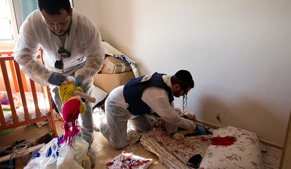 Zaka volunteers clean bloodstains from a pillow and a baby toy in a children's room at an apartment in a building in Kiryat Malachi, Israel, that was hit on Nov. 15, 2012, by a rocket fired from the Gaza Strip. Militants in the Hamas-ruled Gaza Strip killed three Israelis in a rocket attack liable to deepen a bruising Israeli air, naval and artillery offensive against Palestinian rocket squads. The casualties were the first in Israel since it launched its operation the previous day with the assassination of Hamas' top military commander. (Associated Press)