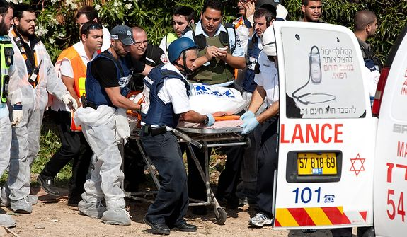 Zaka volunteers and rescue personnel carry the plastic-wrapped body of a victim from an apartment in a building in Kiryat Malachi, Israel, that was hit on Nov. 15, 2012, by a rocket fired from the Gaza Strip. Militants in the Hamas-ruled Gaza Strip killed three Israelis in a rocket attack liable to deepen a bruising Israeli air, naval and artillery offensive against Palestinian rocket squads. The casualties were the first in Israel since it launched its operation the previous day with the assassination of Hamas' top military commander. (Associated Press)