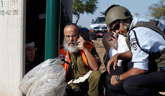 Israeli security personnel take cover in Kiryat Malachi, Israel, on Nov. 15, 2012. Militants in the Hamas-ruled Gaza Strip killed three Israelis in a rocket attack liable to deepen a bruising Israeli air, naval and artillery offensive against Palestinian rocket squads. The casualties were the first in Israel since it launched its operation the previous day with the assassination of Hamas' top military commander. (Associated Press)