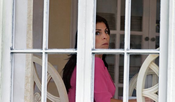 Jill Kelley looks out the window of her home Tuesday, Nov 12, 2012 in Tampa, Fla. Kelley is identified as the woman who allegedly received harassing emails from Gen. David Petraeus' paramour, Paula Broadwell. She serves as an unpaid social liaison to MacDill Air Force Base in Tampa, where the military's Central Command and Special Operations Command are located. (AP Photo/Chris O'Meara)
