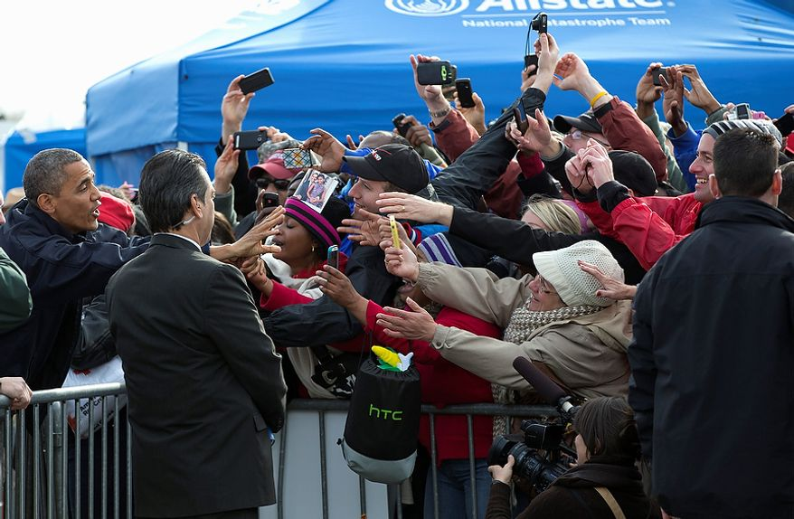 President Barack Obama reaches to greet people at the FEMA recovery center on the grounds of New Dorp High School on the Staten Island borough of New York, Thursday, Nov. 15, 2012. (AP Photo/Carolyn Kaster)