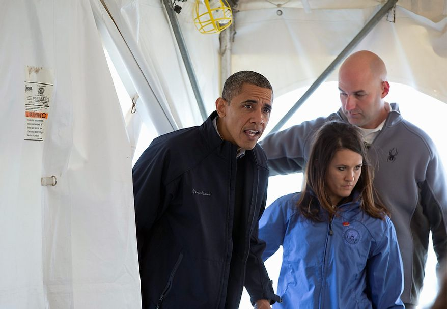 President Barack Obama ducks into a tent  to greet people at a FEMA recovery center on the grounds of New Dorp High School on the Staten Island borough of New York, Thursday, Nov. 15, 2012. (AP Photo/Carolyn Kaster)