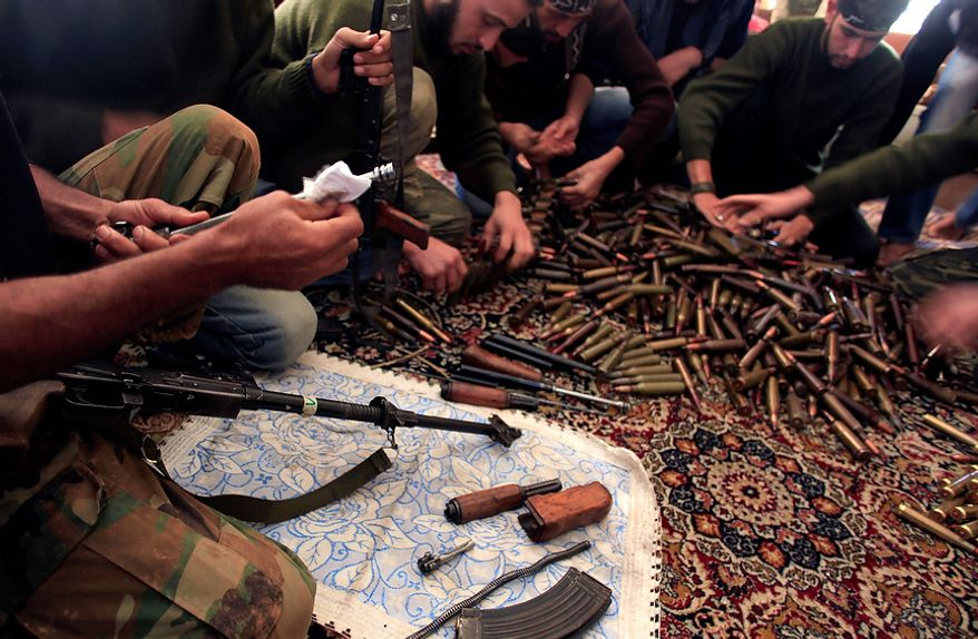 Rebels clean their weapons and check ammunition at their base on the outskirts of Aleppo, Syria, Wednesday, Nov. 14, 2012. (AP Photo/ Khalil Hamra)