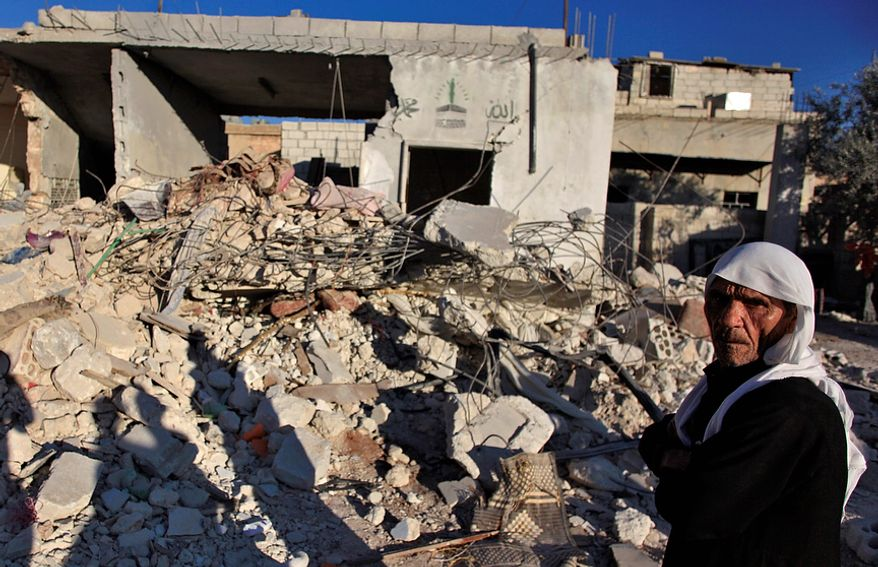An elderly Syrian man walks next to the remains of a house was destroyed by an airstrike last Tuesday killing several Syrians, in the Maret El-Nasaneh village on the outskirts of Idlib, Syria, Wednesday, Nov. 14, 2012. (AP Photo/ Khalil Hamra)