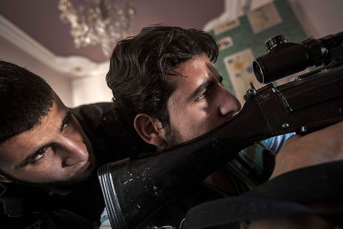 In this Wednesday, Nov. 14, 2012 photo, Syrian rebel fighters keep an eye through a hole in the wall that overlooks a position held by troops loyal to Syrian President Bashar Assad