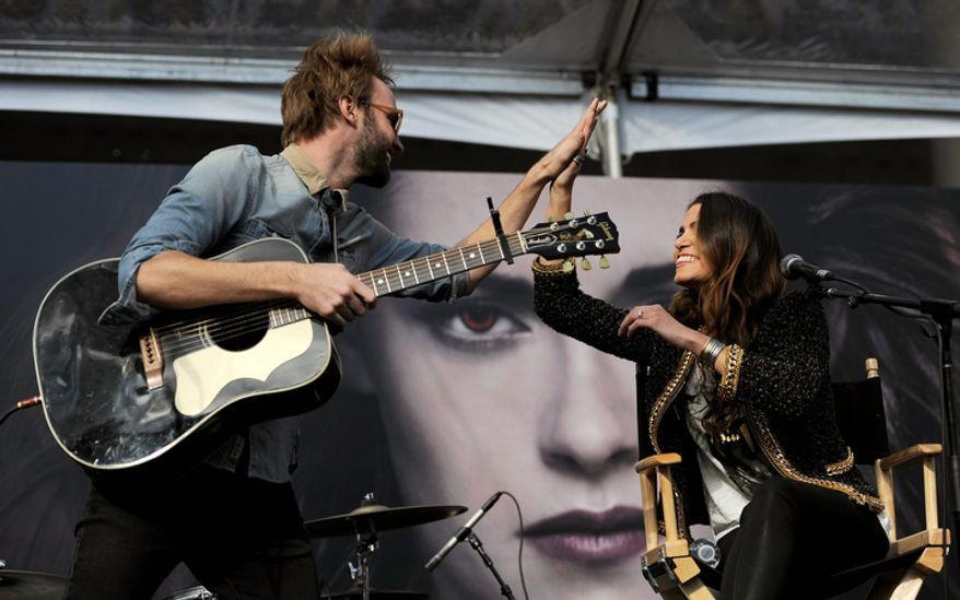 """Nikki Reed, right, a cast member in the film """"The Twilight Saga: Breaking Dawn Part 2,"""" gets a high five from her husband, singer Paul McDonald, after they performed together onstage during the Twilight Fan Camp Concert outside Nokia Theater L.A. Live, Saturday, Nov. 10. 2012, in Los Angeles. The world premiere of the film will be held at Nokia Theater L.A. Live on Monday. (Photo by Chris Pizzello/Invision/AP)"""