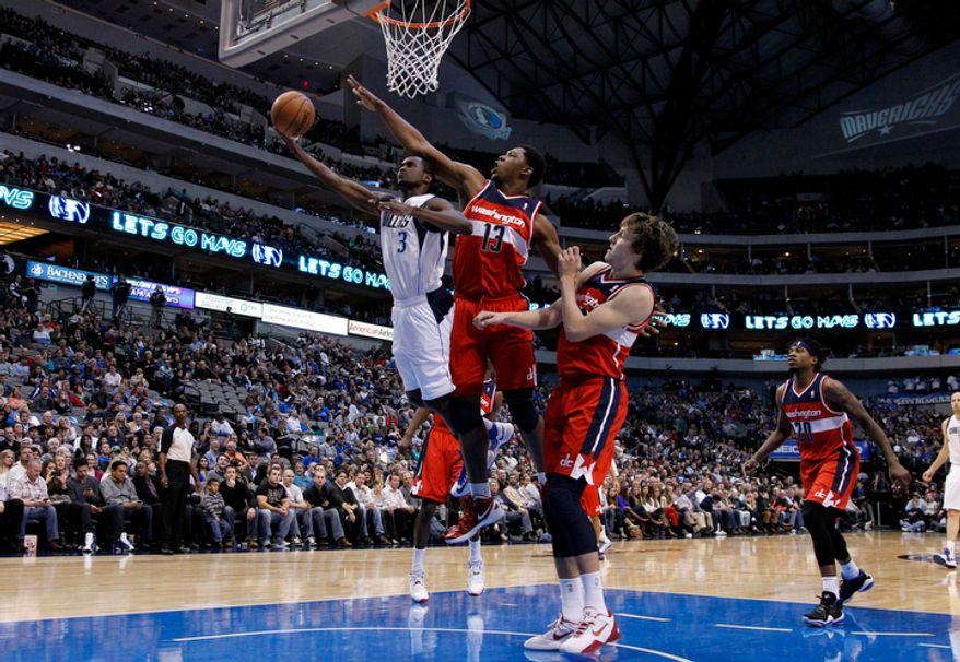 Dallas Mavericks' Rodrigue Beaubois (3) of Guadeloupe attempts a shot as Washington Wizards' Kevin Seraphin (13) of France and Jan Vesely, center right, defend during an NBA basketball game Wednesday, Nov. 14, 2012, in Dallas. The Mavericks won 107-101. (AP Photo/Tony Gutierrez)