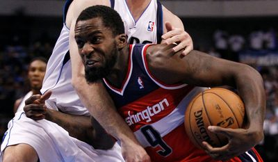 Dallas Mavericks' Troy Murphy (6) wraps up and stops Washington Wizards' Martell Webster (9) on a break away drive to the basket in the first half of an NBA basketball game, Wednesday, Nov. 14, 2012, in Dallas. (AP Photo/Tony Gutierrez)