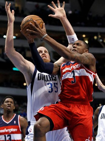 Washington Wizards' Bradley Beal (3) attempts a shot after getting by Dallas Mavericks' Chris Kaman (35) in the first half of an NBA basketball game, Wednesday, Nov. 14, 2012, in Dallas. (AP Photo/Tony Gutierrez)