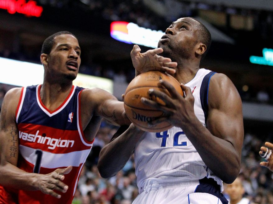 Washington Wizards' Trevor Ariza (1) stops a drive to the basket by Dallas Mavericks' Elton Brand (42) in the second half of an NBA basketball game, Wednesday, Nov. 14, 2012, in Dallas. The Mavericks won 107-101. (AP Photo/Tony Gutierrez)