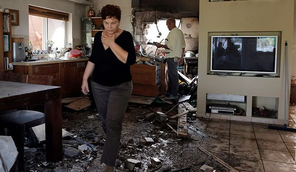 An Israeli woman walks through a damaged house hit by a rocked fired from the Gaza Strip the hit a house near the Israel-Gaza border, Friday, Nov. 16, 2012. Fierce clashes between Israeli forces and Gaza militants are continuing for the third day.(AP Photo/Tsafrir Abayov)