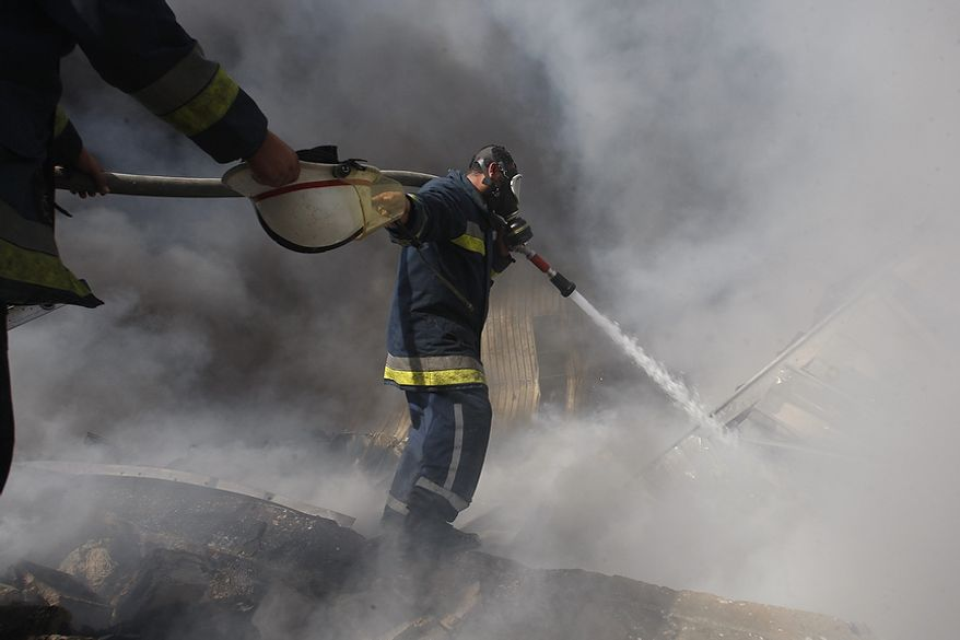 Palestinian firefighters try to extinguish a fire after an Israeli airstrike on a wood factory in east Jabaliya, northern Gaza Strip, Friday, Nov. 16, 2012. (AP Photo/Hatem Moussa)