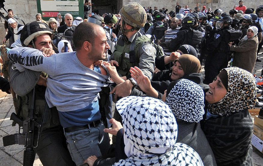 Israeli police detain a Palestinian demonstrator as scuffles broke out between Israeli troops and Muslim worshippers prevented from entering the Al-Aqsa mosque compound for prayers, in Jerusalem's Old City, Friday, Nov. 16, 2012. Israeli police was on high alert on Friday to prevent clashes following Friday prayers.(AP Photo/Mahmoud Illean)
