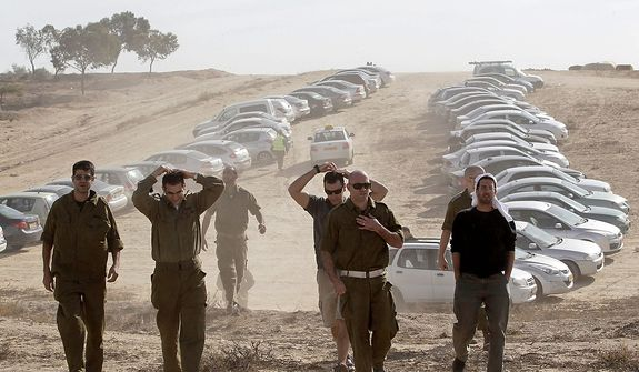 Israeli military reservists arrive at a gathering point in Mishmar Hanegev, southern Israel, Friday, Nov. 16, 2012. The Israeli government approved on Thursday the mobilization of up to 30,000 reservists for a possible ground incursion into Gaza.(AP Photo/Ilan Assayag)