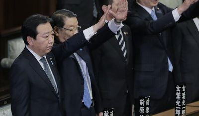 Prime Minister Yoshihiko Noda stands still as Chief Cabinet Secretary Osamu Fujimura, second left, and Foreign Minister Koichiro Gemba, right, raise hands and shout banzai, or long live, after he dissolved the lower house of parliament in Tokyo Friday, Nov. 16, 2012. (AP Photo/Koji Sasahara)