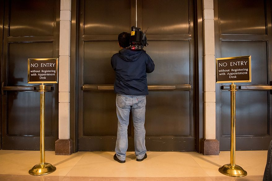 A member of the media films between a crack in a set of double doors as former CIA Director David Petraeus allegedly meets with lawmakers behind closed doors inside the Capitol Visitors Center on Capitol Hill, Washington, D.C., Friday, November 16, 2012. (Andrew Harnik/The Washington Times)