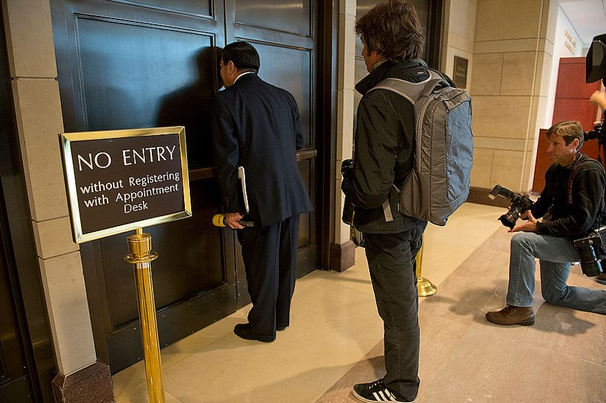 Members of the media try to get a peek inside the hallway down to the room where Gen. David Petraeus testifies about the Benghazi attack behind closed doors at the U.S. Capitol on Friday, Nov. 16, 2012. The general was expected to say that he knew the attack was terror-based from the beginning. (Barbara L. Salisbury/The Washington Times)