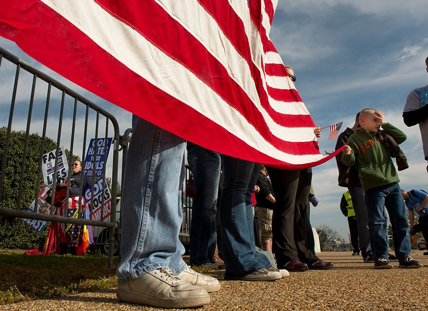 Cameron Coady, 7, of Philadelphia, Pa., right, helps veterans and veteran supporters use an american flag to block protesters with the Westboro Baptist Church, left, outside the main entrance to Arlington National Cemetery on Veterans Day, Arlington, Va., Monday, November 12, 2012. The Westboro Baptist Church, based in Topeka, Kan., is known for extreme views and have caused an uproar over the past few years for their protests. (Andrew Harnik/The Washington Times)