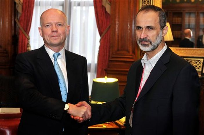 Britain's Foreign Secretary William Hague shakes hands for the cameras with the head of the new Syrian National Coalition for Opposition and Revolutionary Forces Mouaz al-Khatib before a meeting on the continuing conflict in Syria, at the Foreign and Commonwealth office in Whitehall central on Friday, Nov. 16, 2012. (AP Photo/ John Stillwell/Pool)
