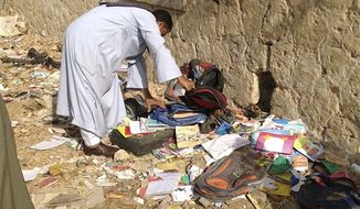 An Egyptian looks through books and school bags that were strewn along the tracks at the scene where a speeding train crashed into a bus carrying children to their kindergarten, killing at least 47, officials said, near Assiut in southern Egypt, Saturday, Nov. 17, 2012. The bus was carrying more than 50 children between 4 and 6 years old when it was hit by a train near al-Mandara village in Manfaloot district in the province of Assiut, a security official said, adding that it appears that the railroad crossing was not closed as the train sped toward it. (AP Photo/Mamdouh Thabet)