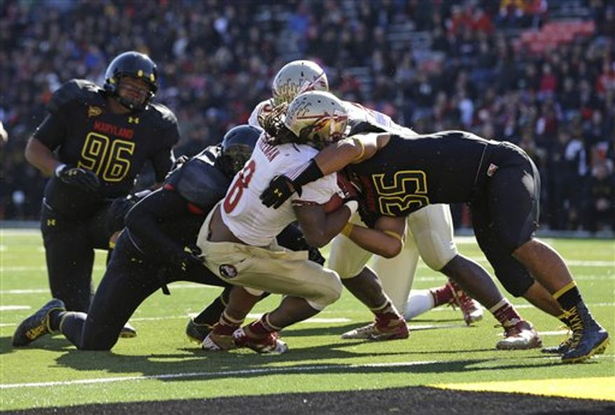 Florida State running back Devonta Freeman, center, pushes into the end zone for a touchdown past Maryland linebacker Alex Twine (35) in the first half of an NCAA college football game in College Park, Md., Saturday, Nov. 17, 2012. (AP Photo/Patrick Semansky)