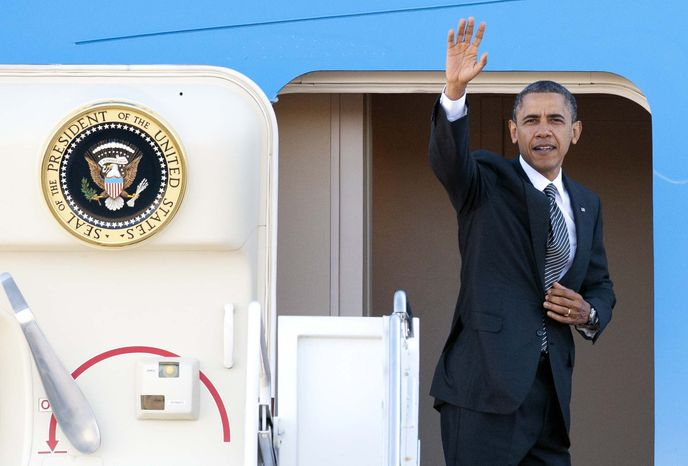 President Barack Obama waves as he boards Air Force One at Andrews Air Force Base, Md., Saturday, Nov. 17, 2012, en route to Southeast Asia. (AP Photo/Cliff Owen)