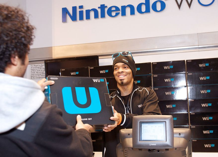 A fan purchases one of the first Wii U systems in the world at the midnight launch event at Nintendo World in New York on Sunday. Wii U is set to change the way people interact with their games, their TVs and each other. The Wii U is designed to appeal to the casual audience and the hard-core gamers. (Associated Press)