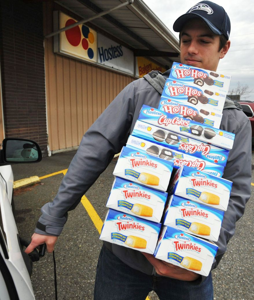 Andy Wagar loads some of the last Hostess products into a van outside the Wonder Bakery Thrift Shop in Bellingham, Wash., on Friday after the century-old company said it would shutter operations. (Associated Press)