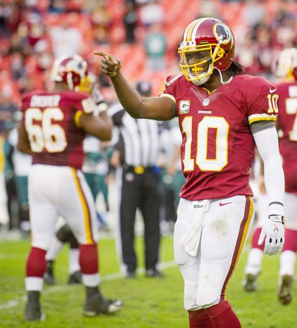 Washington Redskins quarterback Robert Griffin III (10) smiles and points to the sideline as the offense takes the field to run out the clock at the end of the fourth quarter as the Washington Redskins defeat the Philadelphia Eagles 31-6 at FedEx Field, Landover, Md., Sunday, Nov. 18, 2012. (Andrew Harnik/The Washington Times)