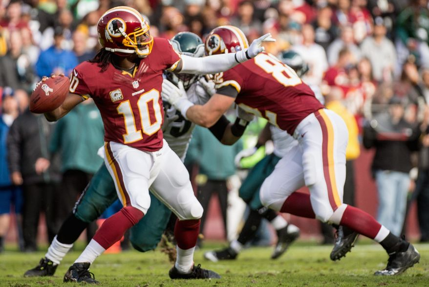 Redskins rookie quarterback Robert Griffin completed 14 of 15 passes, a 93.3 completion percentage, for 200 yards and four touchdowns. His quarterback rating was a perfect 158.3. Griffin, enjoying a light moment during the fourth quarter (below) also rushed 12 times for 84 yards. (Andrew Harnik/The Washington Times)
