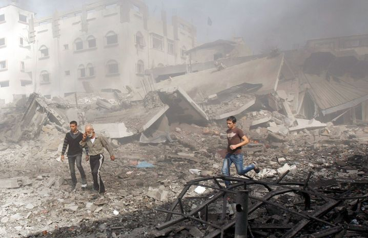Palestinians hurry away from a damaged building after an Israeli airstrike in Gaza City, Gaza Strip, on Sunday. Israel widened the range of targets in its Gaza offensive Sunday, striking more than a dozen homes of suspected Hamas militants. (Associated Press)