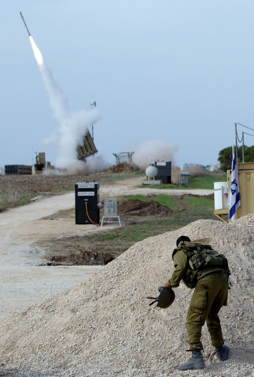 An Israeli soldier watches as an Iron Dome missile is launched Sunday near Ashdod, Israel.  (Associated Press)