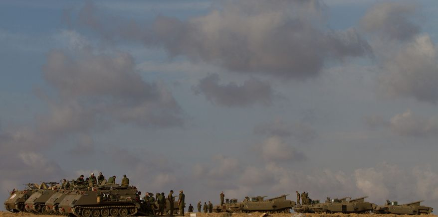 Israeli soldiers gather with their armored personnel carriers in a staging area near the Israel-Gaza Strip border on Sunday. Israel is considering a ground invasion of the Gaza Strip in response to rocket attacks by Hamas militants, but says it would prefer not to do so. (Associated Press)