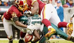 Staunch defense was displayed throughout as Redskins strong safety DeJon Gomes (24) and inside linebacker London Fletcher break up a pass intended for Eagles wide receiver Jeremy Maclin (shown) in the fourth quarter. (Andrew Harnik/The Washington Times)
