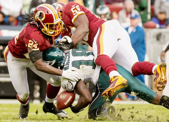 Staunch defense was displayed throughout as Redskins strong safety DeJon Gomes (24) and inside linebacker London Fletcher break up a pass intended for Eagles wide receiver Jeremy Maclin (shown) in the fourt