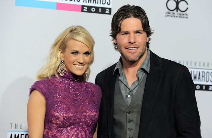 ** FILE ** Carrie Underwood, left, and Mike Fisher arrive at the 40th Anniversary American Music Awards on Sunday, Nov. 18, 2012, in Los Angeles. (Photo by Jordan Strauss/Invision/AP)