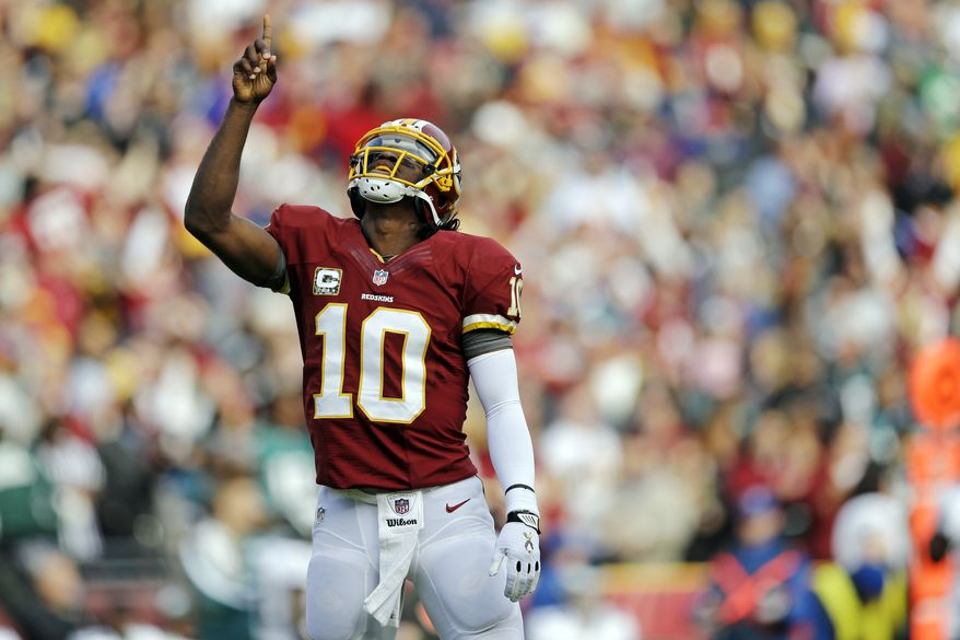 Washington Redskins quarterback Robert Griffin III points toward the sky after throwing a touchdown pass to wide receiver Aldrick Robinson during the first half of an NFL football game against the Philadelphia Eagles in Landover, Md., Sunday, Nov. 18, 2012. (AP Photo/Patrick Semansky)