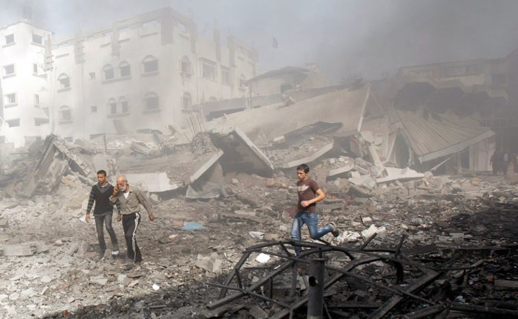 Palestinians hurry away from a damaged building after an Israeli air strike in Gaza City, Sunday, Nov. 18, 2012. Israel widened the range of targets in its Gaza offensive Sunday, striking more than a dozen homes of suspected Hamas militants and two media offices,