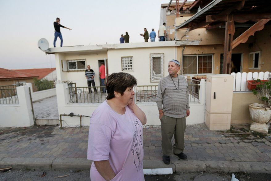 Residents inspect the damage at a house after a rocket fired by Palestinian militants from inside the Gaza Strip, landed at the community of Ofakim, in southern Israel. According to reports, two Israelis were wounded and their condition is unknown. Israel launched the operation last Wednesday by assassinating Hamas' military chief and carrying out dozens of airstrikes on rocket launchers and weapons storage sites.  (AP Photo/Lefteris Pitarakis)