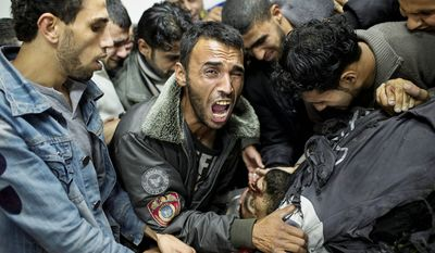 A Palestinian man cries next the body of a dead relative in the morgue of Shifa Hospital in Gaza City. (AP Photo/Bernat Armangue)