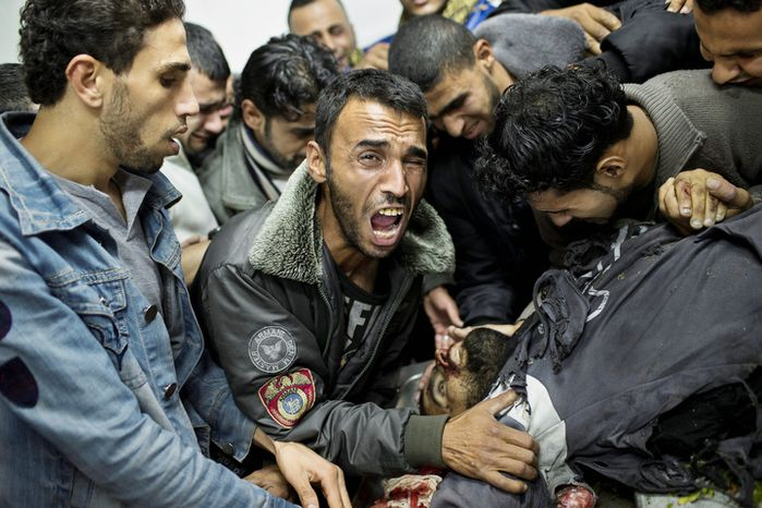 A Palestinian man cries next the body of a dead relative in the morgue of Shifa Hospital in Ga