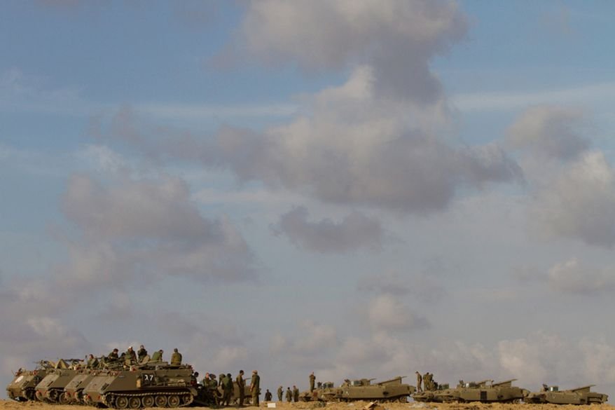 Israeli soldiers gather with their armored personnel carriers in a gathering area near the Israel Gaza Strip border, in southern Israel, Sunday, Nov. 18, 2012.  (AP Photo/Ariel Schalit)
