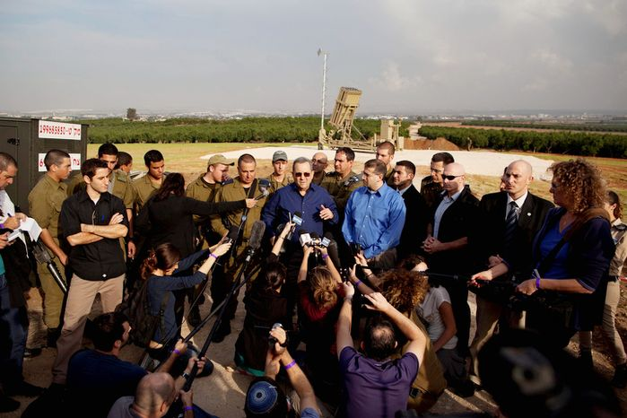 Israeli Defense Minister Ehud Barak, center left, and US ambassador to Israel Dan Shapiro, center right, speak to journalists in front of a military Iron Dome defense missile system, designed to intercept and destroy incoming short-range rockets and artillery shells, near the costal city of Tel Aviv. (AP Photo/Oded Balilty)