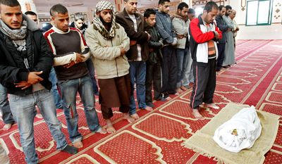 Palestinians pray over the body of one and a half year-old baby, Iyad Abu Khoussa, during his funeral at a mosque in Bureij Refugee Camp, central Gaza Strip. The baby boy was one of five Palestinian children killed in Israeli strikes on Sunday, according to a Gaza health official. (AP Photo/Adel Hana)